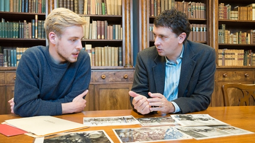 MAX WIELAND '17, and Associate Professor of History Edward Miller discuss photos for the Dartmouth Vietnam Project